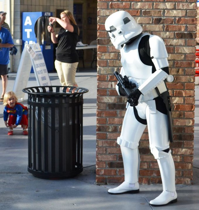 A little girl dressed as Supergirl is looking up at a Stormtrooper cosplayer pretending to hide behind a wall
